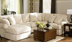 The image shows a white sectional sofa with loose back cushions and throw pillows.